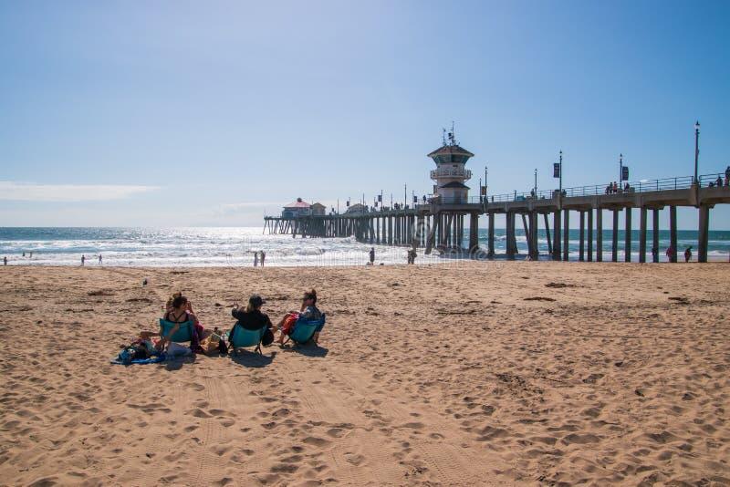 Huntington Beach, Kalifornien - 11. Oktober 2018: Frau drei, die auf Stühlen auf einem einsamen Strand spricht und betrachtet ein stockfotos