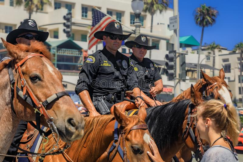 Equestrian police officers from Huntington Beach and Santa Ana Police Departments in front of the Huntington Beach Pier. Huntington Beach, USA - July 03, 2017 royalty free stock images