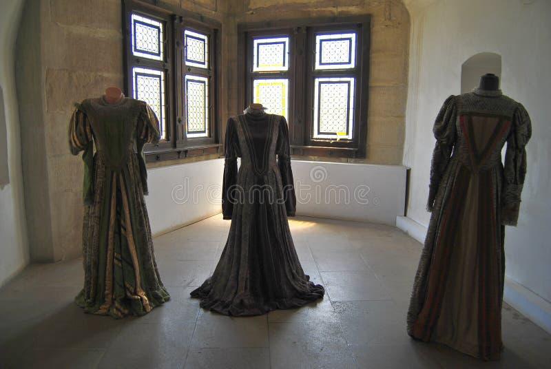 Hunyadi Castle - dresses. View of gorgeous renaissance historical dresses beautifully displayed inside the Hunyadi Castle Medieval window in Hunyadi Castle stock image