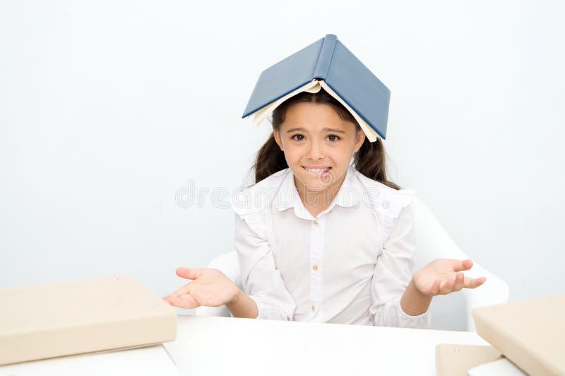 Hur är det som är möjligt att lära Förvirrat utmattat för flickabarn med boktaket på head vit bakgrund Skolflicka som tröttas av royaltyfria foton