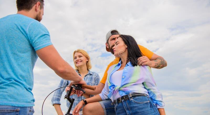 Hur cykeln ändrade samhälle Gruppvänner hänger ut med cykeln Stilfulla ungdomarspenderar för företag himmel för fritid utomhus arkivfoto