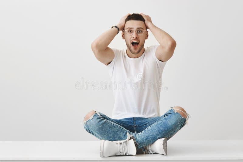 Hur kunde du göra sådant ting Chockad och skövlad manlig student i exponeringsglas som sitter med korsade ben på golvinnehav arkivfoto