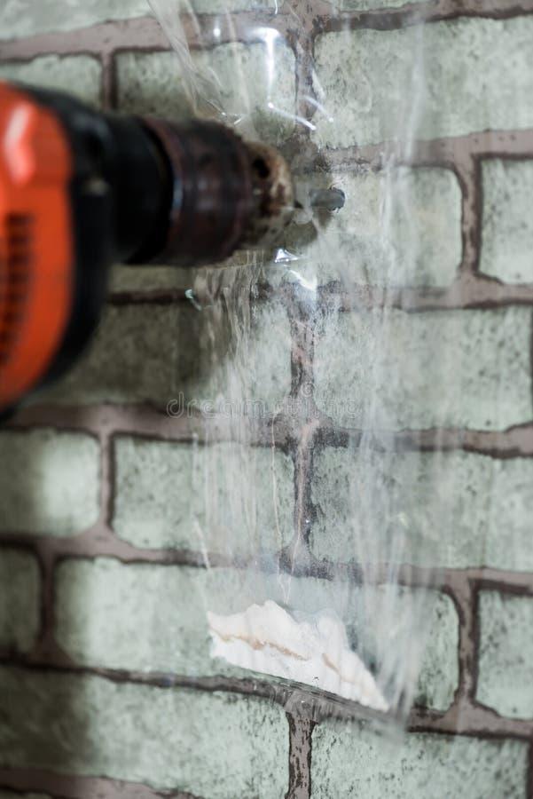 Hur man borrar väggen, genom att skydda som är dammigt i rummet arkivbild