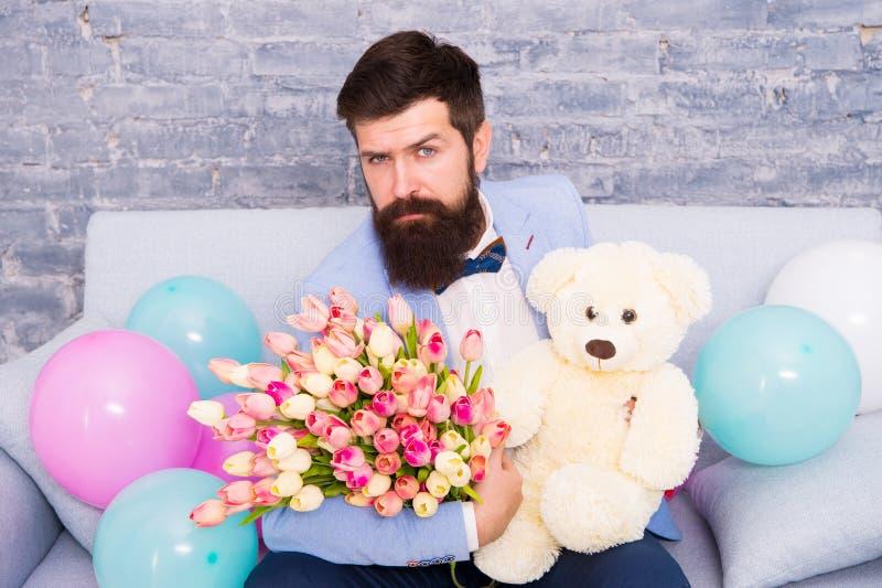 Hur man fr?gar hennes datumm?rkning Den romantiska mannen med blommor och nallebj?rnen sitter p? v?ntande flickv?n f?r soffa Roma arkivbild
