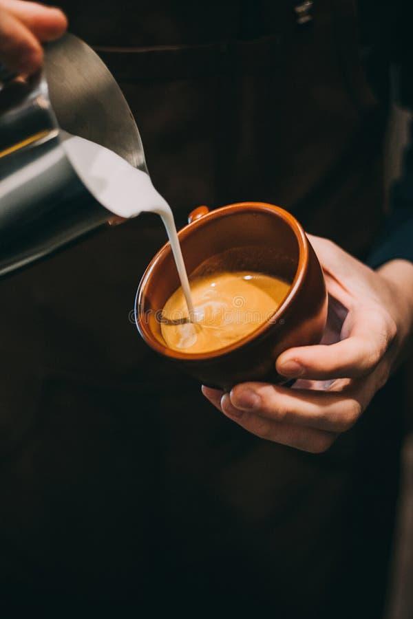 Hur man gör lattekonst vid baristafokusen in att mjölka och kaffe royaltyfri foto