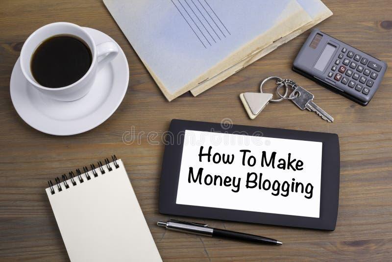 Hur man gör pengar som blogging Smsa på minnestavlaapparaten på en träta royaltyfria bilder