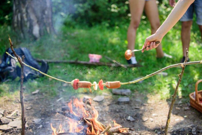 Hur man grillar korvar med grönsaker Korvar på pinnebrasabakgrund Rökig lukt av grillad mat Varm och skön Roasty arkivfoto