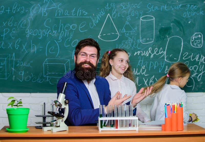 Hur man intresserar barn f?r att studera Fascinera biologikurs Skolal?rare av biologi Skäggigt lärarearbete för man med fotografering för bildbyråer