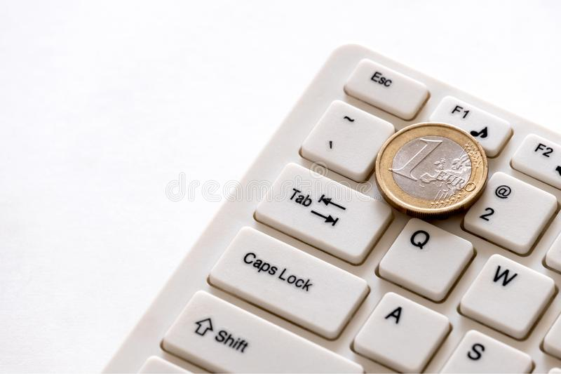 Hur mycket gör programmerare i Europa tjänar Euromyntet ligger på tangenten med numret ett på ett datortangentbord Begrepp av fin royaltyfri fotografi