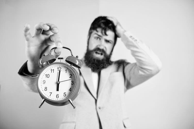 Hur mycket tid l?mnade brukar stopptid tid att fungera F?r aff?rsmanh?ll f?r man sk?ggig stressig klocka Aggressiv ung man hipste fotografering för bildbyråer