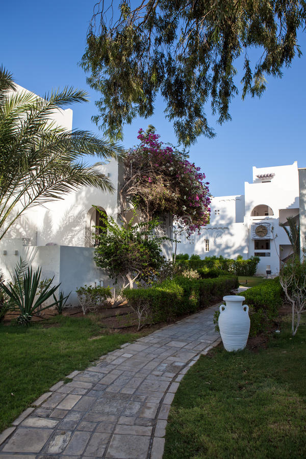 Hurgada, Egypt - 11 August 2014: white wall hotel entrance area with path, palms in the idyllic green garden royalty free stock photo