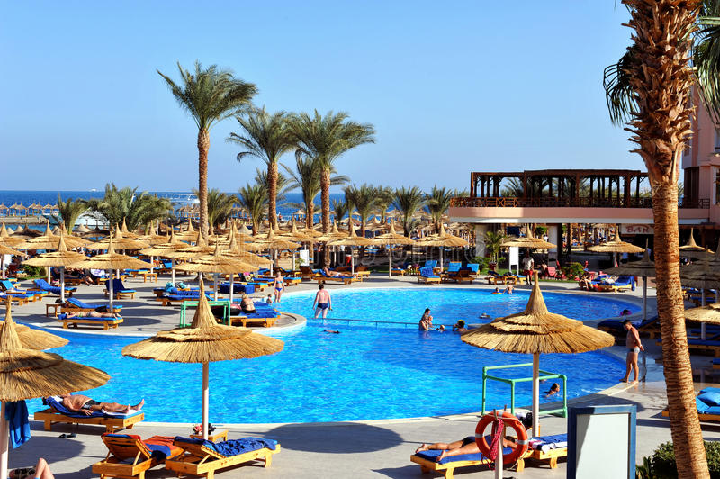 HURGHADA, EGIPTO - 14 DE OCTUBRE DE 2013: La gente no identificada nada y toma el sol en la piscina en un centro turístico tropic foto de archivo libre de regalías