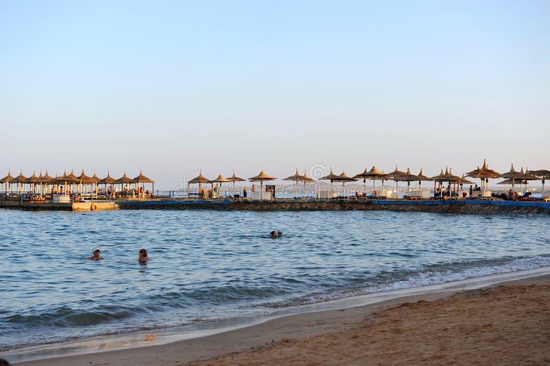 HURGHADA, EGIPTO - 14 DE OUTUBRO DE 2013: O Sandy Beach completamente dos povos está no litoral do Mar Vermelho Estância luxuosa  fotografia de stock royalty free