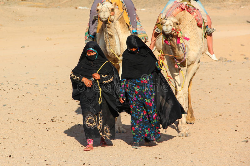 HURGHADA, EGYPT - Apr 24 2015: The old and young women-cameleers from Bedouin village in Sahara desert with their camels, Egypt. HURGHADA on Apr 24, 2015 stock photography