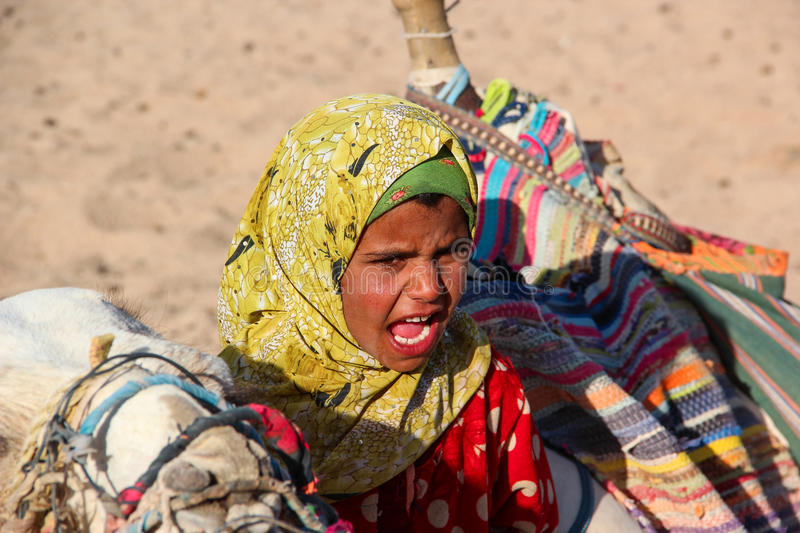 HURGHADA, EGYPT - Apr 24 2015: The young girl-cameleer from Bedouin village in Sahara desert with her camel, shouting inviting. Tourists, Egypt, HURGHADA on Apr stock image