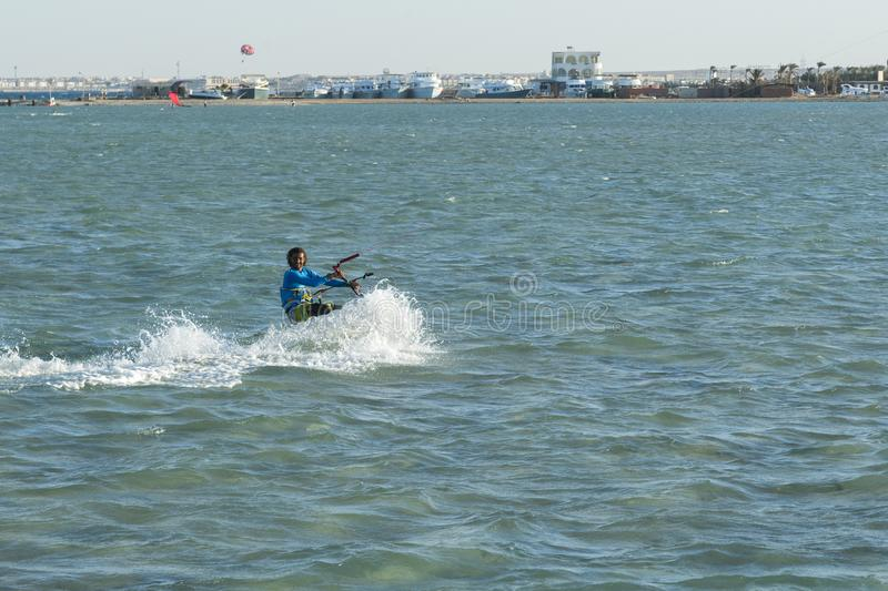 Hurghada, Egypt. November 19 2018 Kitesurfing Kiteboarding action photos man among waves quickly goes. A kite surfer rides the. Waves royalty free stock photo