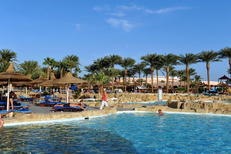 HURGHADA, EGYPTE - OKTOBER 14, 2013: De niet geïdentificeerde mensen zwemmen en zonnebaden in het zwembad bij een luxe tropische  stock foto