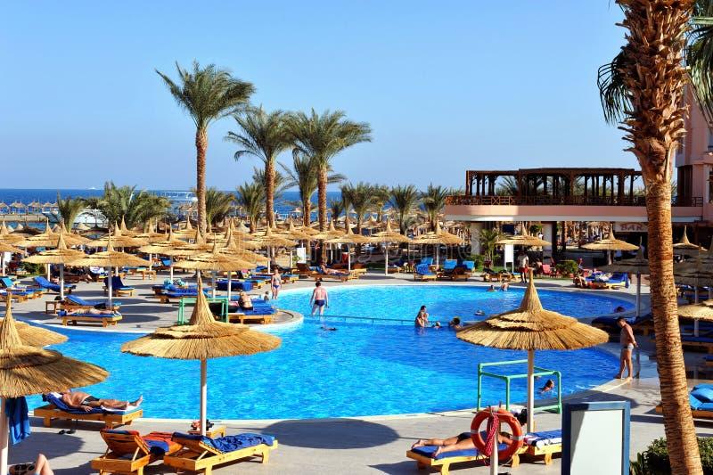 HURGHADA, EGYPTE - OKTOBER 14, 2013: De niet geïdentificeerde mensen zwemmen en zonnebaden in het zwembad bij een luxe tropische  royalty-vrije stock foto