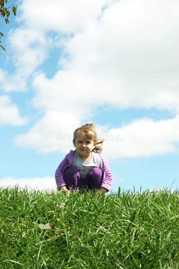 Hurkend Meisje op Heuvel met Wolken stock afbeelding