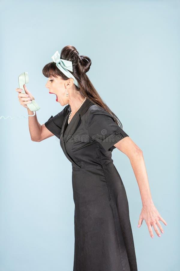 Hurlement de la rétro femme dans la robe noire avec le récepteur de téléphone photos libres de droits