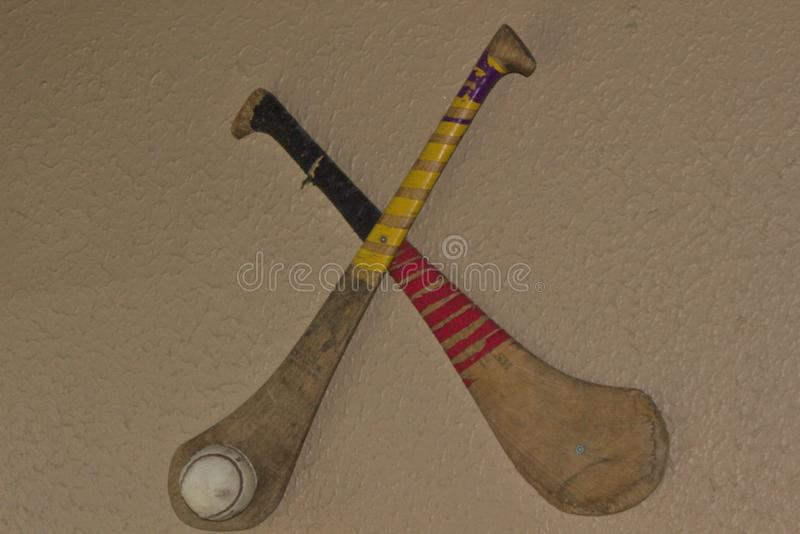 Hurling yellow and red. Crossed hurling sticks and ball one yellow and one red stock photography