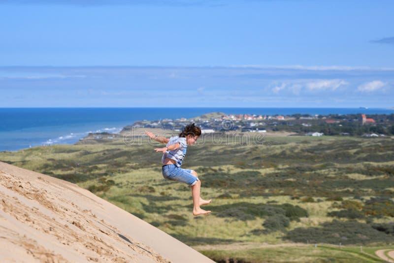 Hurra den lyckliga och glade asiatiska kvinnan som hoppar från klippkanten för bergmaximum, Danmark arkivfoton
