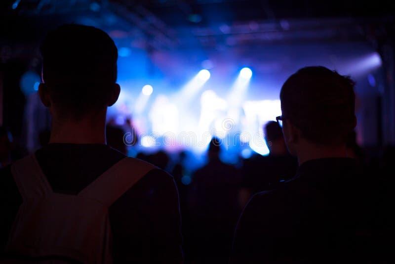 Hurra folkfolkmassan i konsertshowen som har gyckel och applåd framme av etappljus arkivfoto