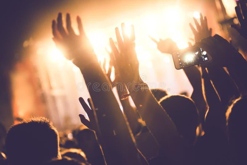 Hurra folkmassan med händer i luft på musikfestivalen arkivfoto