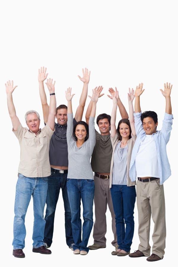 Hurra gruppen av vänner som lyfter deras armar arkivfoton