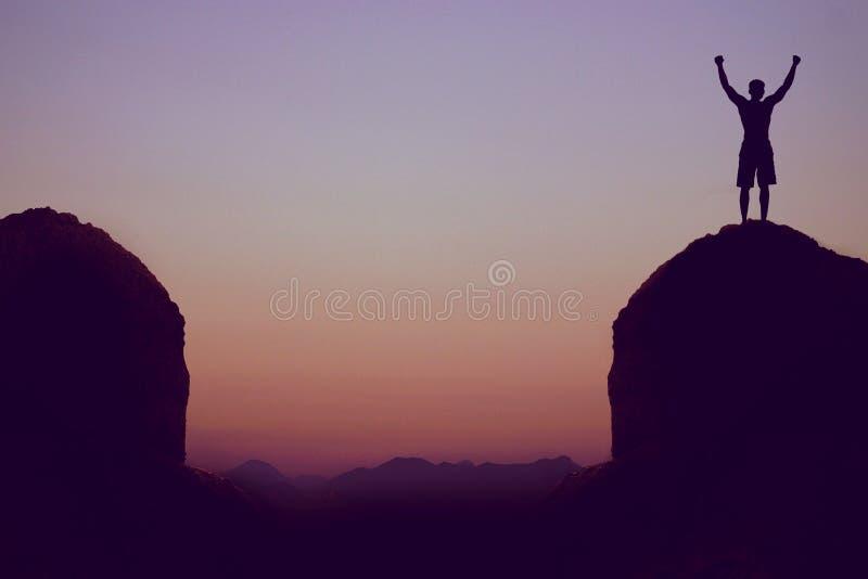 Hurra mannen i berg som symbolet för framgång royaltyfri fotografi