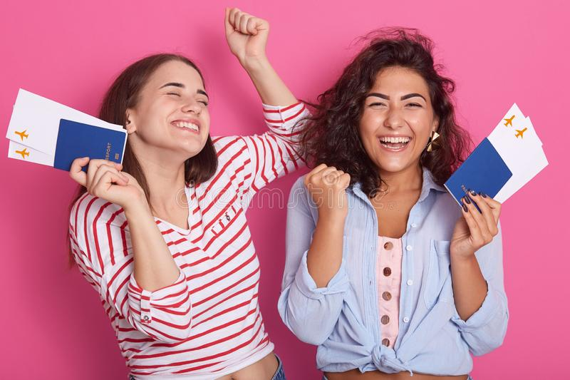 Hurray, vacation! Women holding tickets and passports in hands over rose studio background, ladies clenching fists, expresing. Happyness, dreams come true stock photo