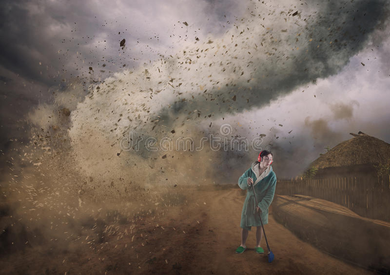 Hurricane clean. Careless man doing housework while his house is destroyed by a hurricane royalty free stock photos