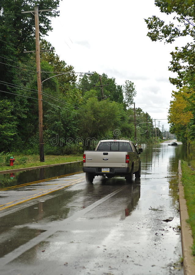 Hurricane Irene aftermath in the Philadelphia area. BENSALEM, PA - AUGUST 28: A pick-up truck heads into a flooded roadway despite the presence of an abandoned royalty free stock image