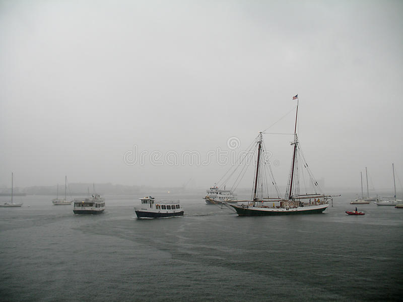 Hurricane Irene drenches Boston Harbor. Hurricane Irene approaching downtown Boston and Boston Harbor with dark clouds and downpours. Boats in the harbor royalty free stock photo