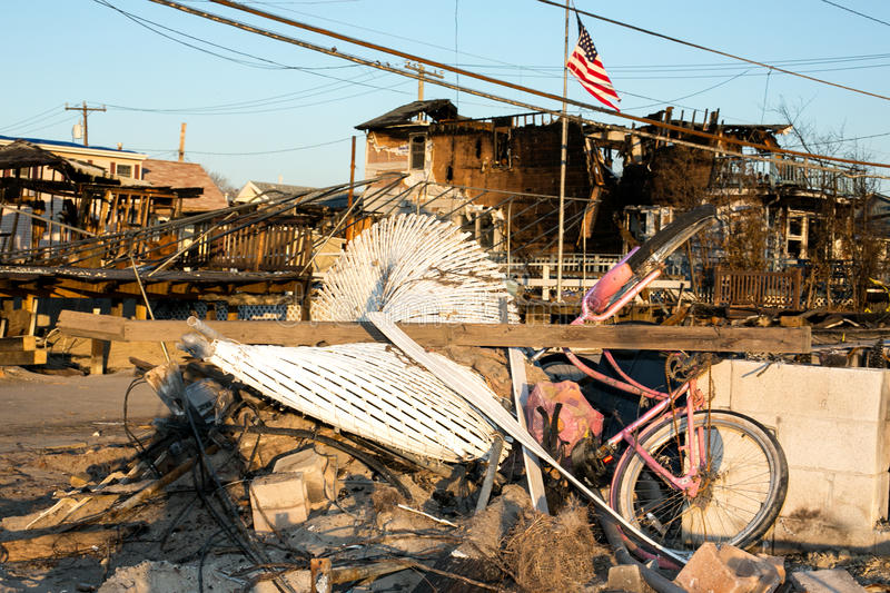 Hurricane Sandy burnt debris, Breezy Point, Queens. Pink Bike and white fence amidst burnt debris where a neighborhood in Breezy Point, Queens was destroyed by royalty free stock image