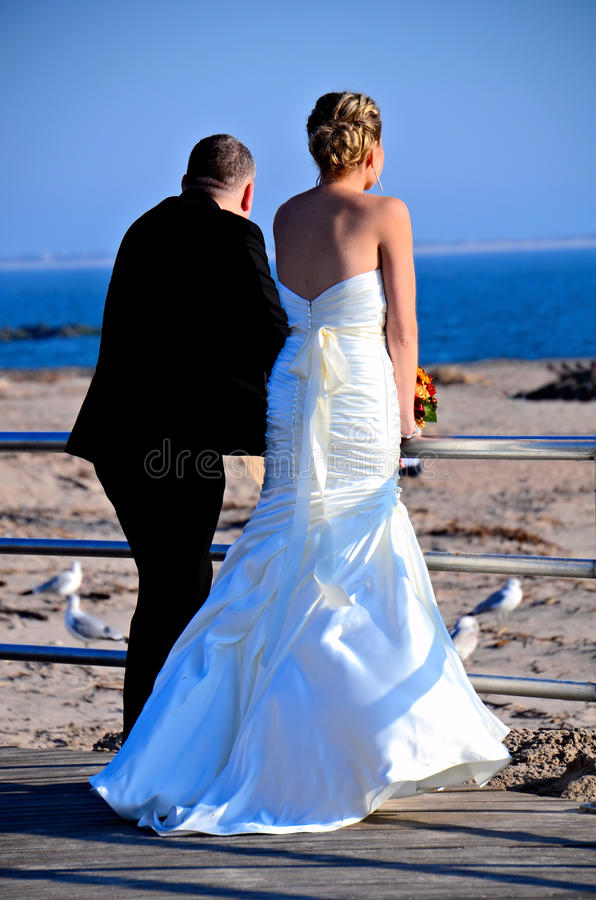 Hurricane Sandys Aftermath. Life goes on. Newly married couple contemplating Brighton Beach, 2 weeks after Hurricane Sandy hit New York area on October 29, 2012 royalty free stock image