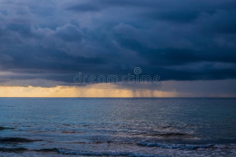 Hurricane storm with thick big dark clouds approaching beach in Florida over the ocean. stock photo