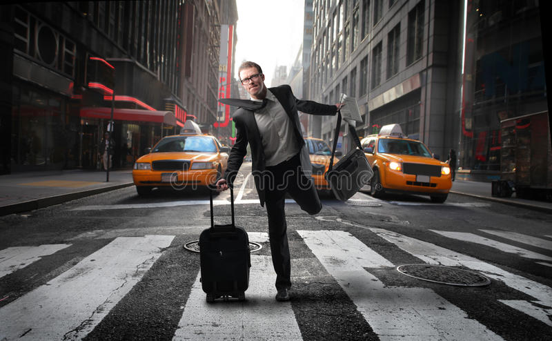 Hurry. Portrait of a businessman quickly crossing a city street with some luggage in his hands