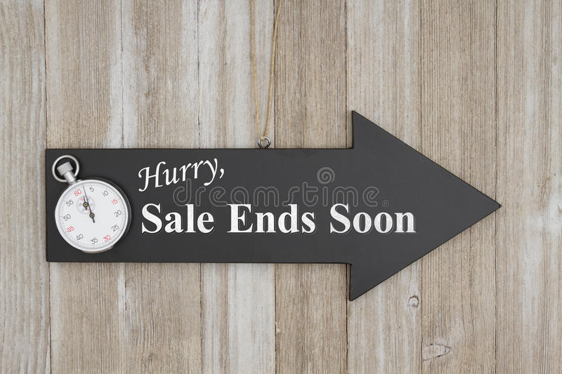 Hurry Sale ends soon sign. Hurry Sale ends soon text on an arrow chalkboard sign with a stopwatch on weathered wood royalty free stock photo