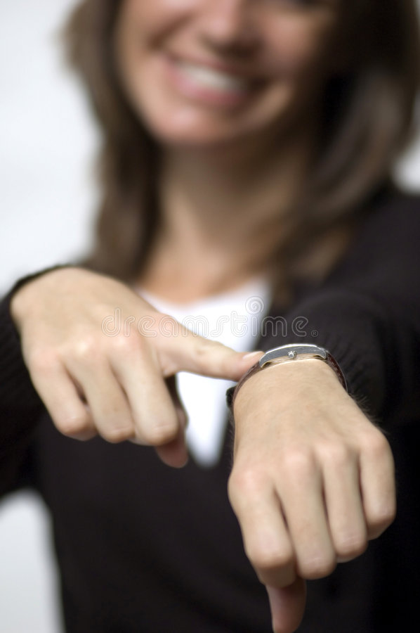 Hurry up. Isolated black amd white female model pointing to her watch royalty free stock photos