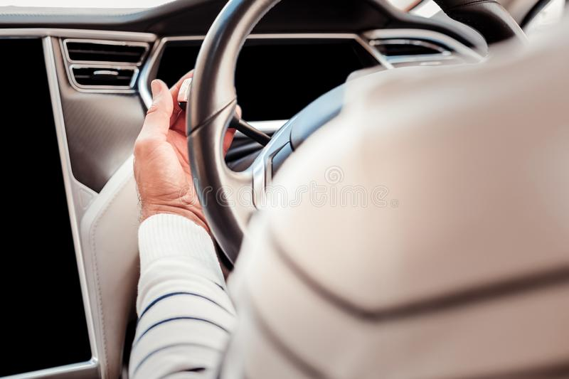 Handsome man driving his car. Hurry up. Close up of male hand that touching wheel, driver sitting with back on camera royalty free stock photo