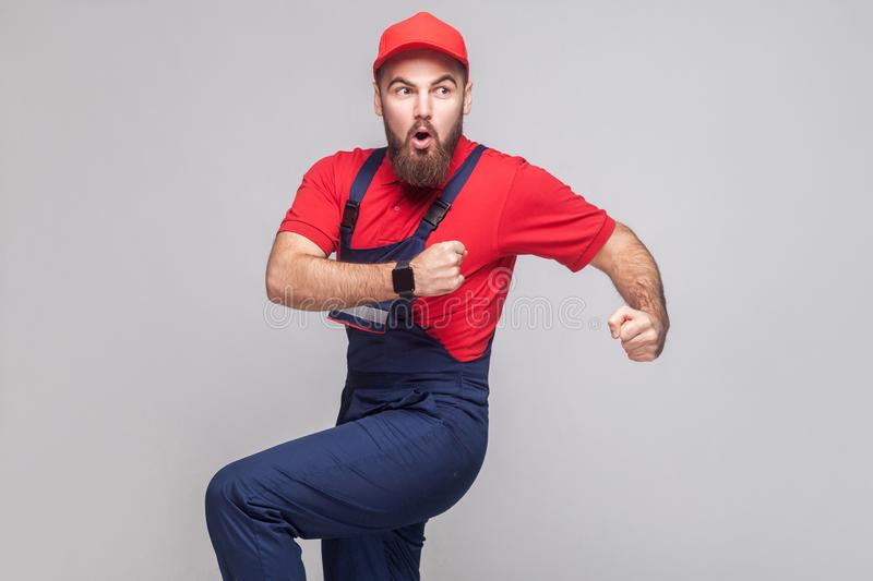 Hurry up! Young amazed handyman with beard in blue overall, red. T-shirt and cap are late and starting to run for help on time. Grey background, indoor, studio royalty free stock image