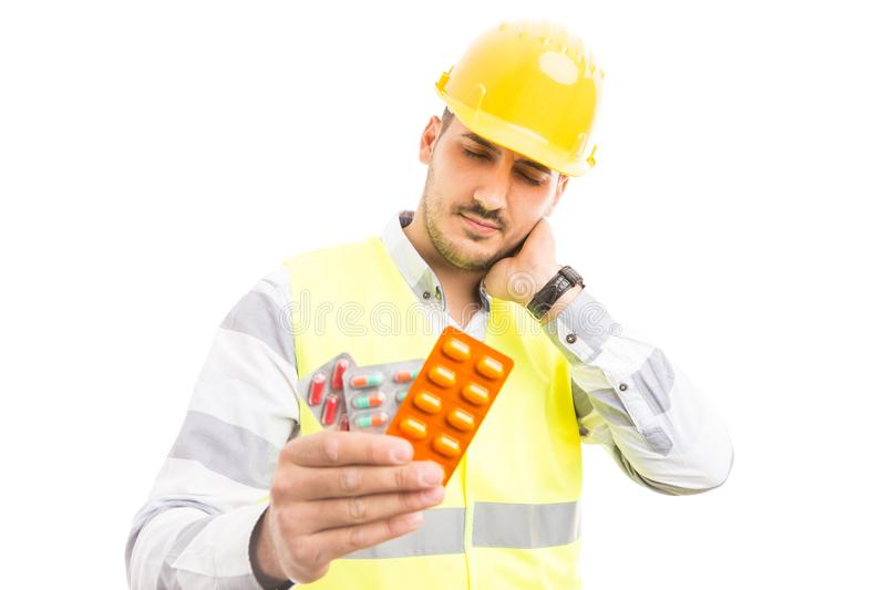 Hurt engineer or constructor holding pills blisters royalty free stock photography