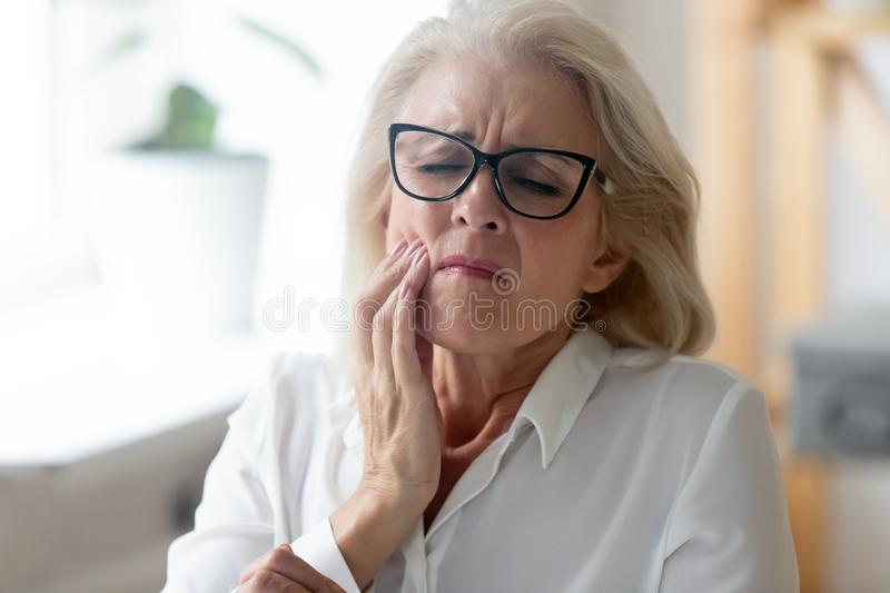 Unhealthy senior woman touch cheek suffering from toothache royalty free stock photo