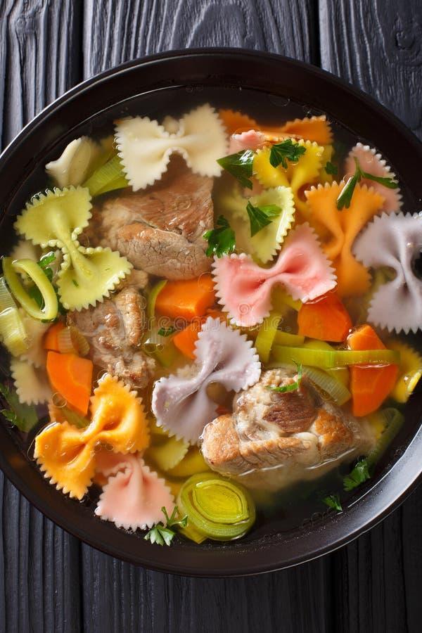 Hurtig köttsoppa, med kulöra farfallepasta- och grönsakclo arkivbild