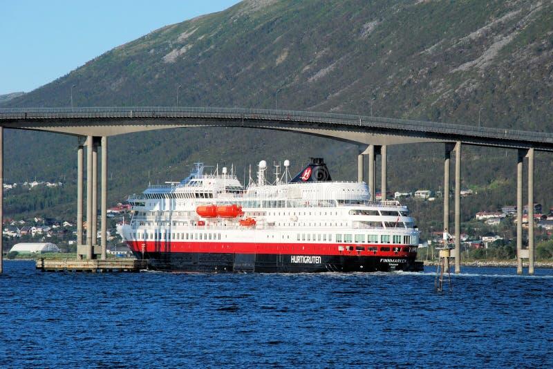 Tromso - Hurtigruten under the Tromso bridge - cruise service along Norways coast. Tromso - Hurtigruten - cruise service along Norways coast under the Tromso royalty free stock photo
