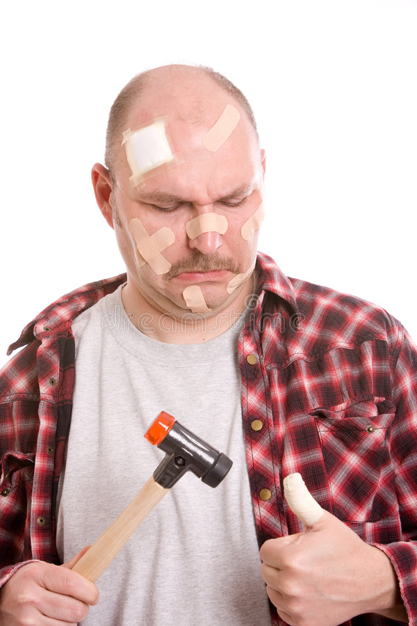 Hurting his thumb. Adult man having hit his thumb with the hammer royalty free stock photo