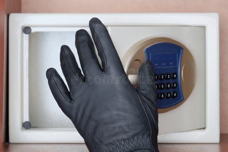 Hurto de objetos de valor y del dinero Un ladr?n negro-con guantes abre la puerta segura con una cerradura de combinaci?n Segurid imagenes de archivo
