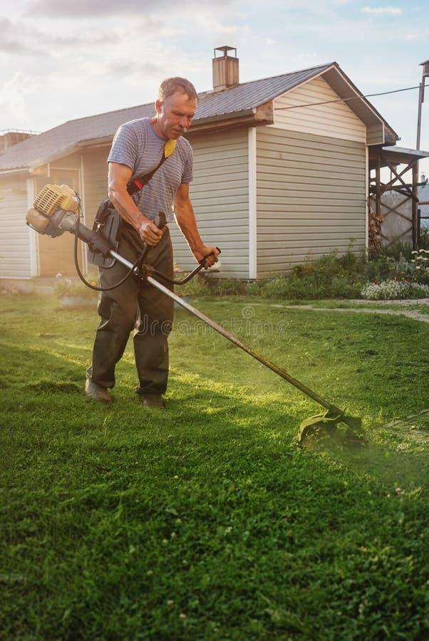 Husägaren klipper hans gräs med en radbeskärare arkivbild