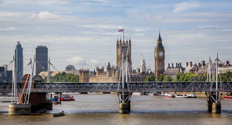 Hus av parlamentet och Big Ben med de Hungerford och femtioårsjubileumbroarna i London, UK arkivbild